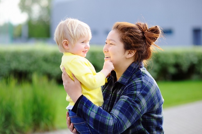 young asian woman with caucasian boy