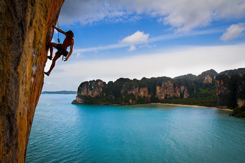 rock climber hanging from a cliff in Railay Beach Thailand