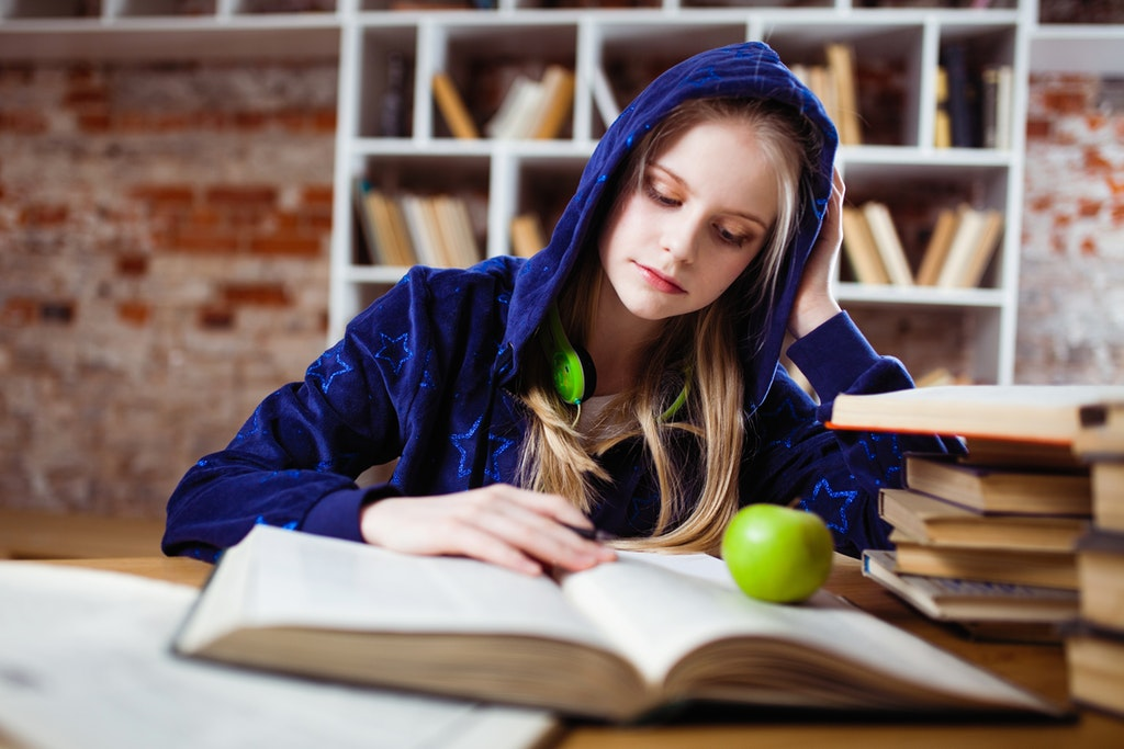 woman studying with green apple on the book